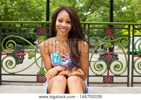 young woman sitting in the park smiling