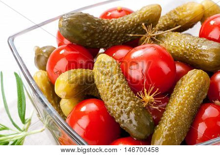 pickled vegetables gherkins and cherry tomatoes in glass bowl close-up on white background