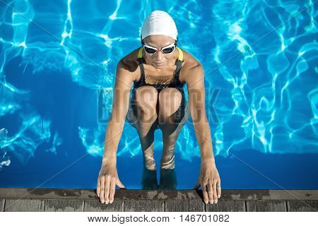 Charming swimmer in the swimming pool. Woman wears a black-lime swimsuit, a white swim cap and swim glasses. She looks forward and holds her hands on the pool side. Outdoors. Horizontal.