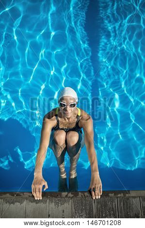 Smiling swimmer in the swimming pool. Woman wears a black-lime swimsuit, a white swim cap and swim glasses. She looks into the camera and holds her hands on the pool side. Outdoors. Vertical.