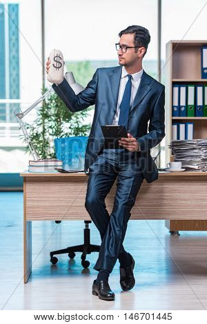 Happy businessman with money sacks in the office