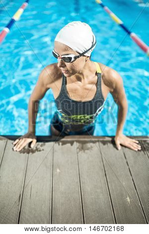 Stylish female swimmer in the swimming pool. Woman wears a multi-colored swimsuit, a white swim cap and swim glasses. She looks to the right and lifted on hands on the pool side. Outdoors. Vertical.