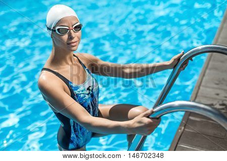Smiling sportive girl stands on the pool ladder in the swim pool and holds hands on it. She wears a blue-black swimsuit, a white swim cap and swim glasses. Woman looks into the camera with a smile.