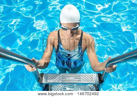 Sportive girl stands on the pool ladder in the swim pool and holds hands on it. She wears a blue-black swimsuit, a white swim cap and swim glasses. Shoot from the top. Outdoors. Horizontal.
