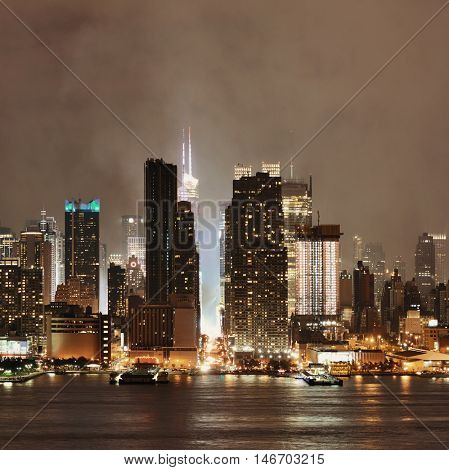 Manhattan midtown skyscrapers and New York City skyline at night with fog