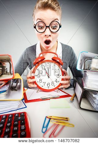 Paper work against time. Young expressive woman in office with big red clock. Unhappy businesswoman so far to ending her work.