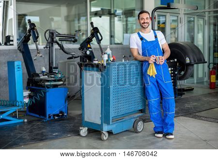 Smiling male engineer in an auto repair shop