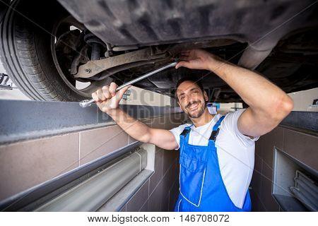 Happy mechanic working on wheel underneath car