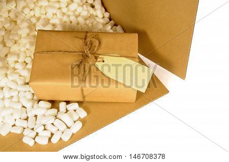 Cardboard box with brown paper package and polystyrene packing pieces.