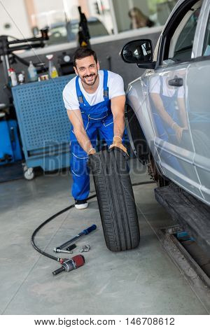 smiling mechanic repair and  pushing a black tyre in workshop