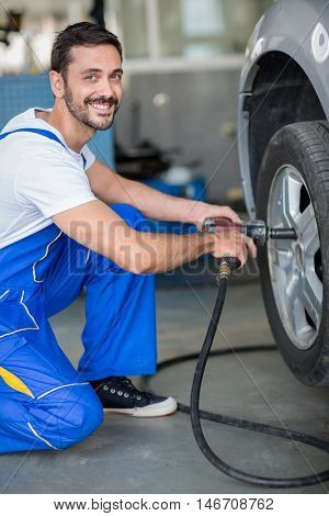 smiling mechanic changing tyre on car wit hydraulic wrench
