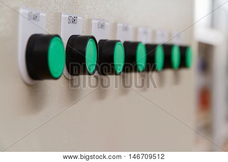 Green start buttons on control panel of automatic machine.