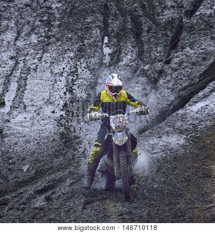 motorcyclist overcomes the obstacle of mud down the mountain