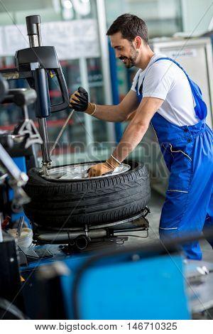 mechanic repairman balancing  car wheel on balancer