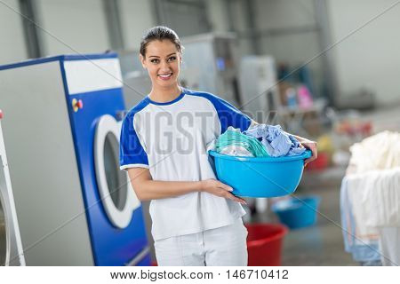 Smiling woman holding laundry basket with clean clothes