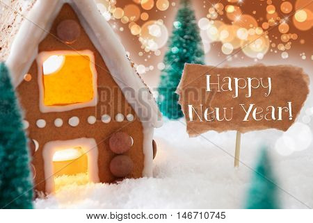 Gingerbread House In Snowy Scenery As Christmas Decoration. Christmas Trees And Candlelight For Romantic Atmosphere. Bronze And Orange Background With Bokeh Effect. English Text Happy New Year