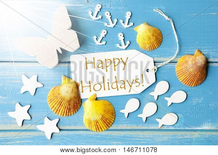 Flat Lay View Of Label With English Text Happy Holidays. Sunny Summer Greeting Card. Butterfly, Shells And Fishes On Blue Wooden Background