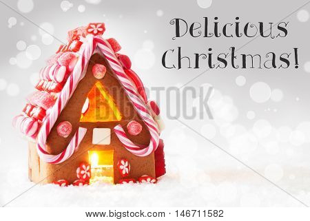 Gingerbread House In Snowy Scenery As Christmas Decoration. Candlelight For Romantic Atmosphere. Silver Background With Bokeh Effect. English Text Delicious Christmas