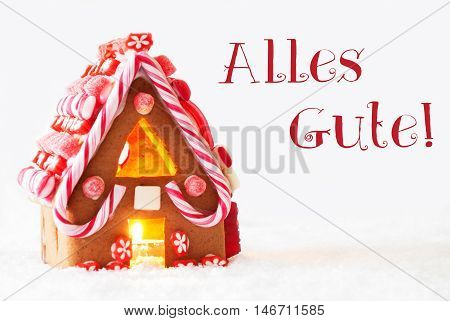 Gingerbread House In Snowy Scenery As Christmas Decoration With White Background. Candlelight For Romantic Atmosphere. German Text Alles Gute Means Best Wishes