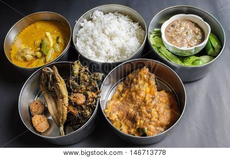 Thai food in food carrier Thai style,fried fish,chicken curry ,chili shrimp paste sauce,vegetable,stream rice,Thai Omelette,Curried shrimp fried