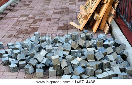 Pile of gray and blue bricks and fragments of wooden scaffolding on unfinished path during construction or repair. Image can be used as a background/