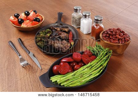 lunch of grilled meat served on black iron pan with asparagus pickles tomatoes olives hot black red pepper salt on wooden table