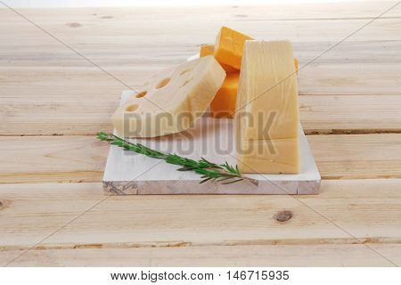 various types of fresh raw aged delicatessen cheese on white plate over light wooden table cheddar swiss
