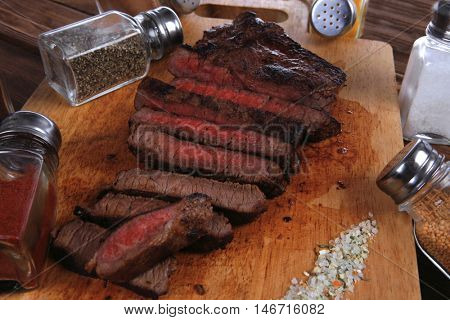 fresh roast red beef meat fillet mignon cut on wooden plate with many different kinds of dry spices red hot paprika crushed black pepper salt dry mustard grains over table