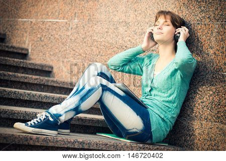 Young woman listening music in Headphones. Beautiful young female student.  Woman sitting on stairs in city park.
