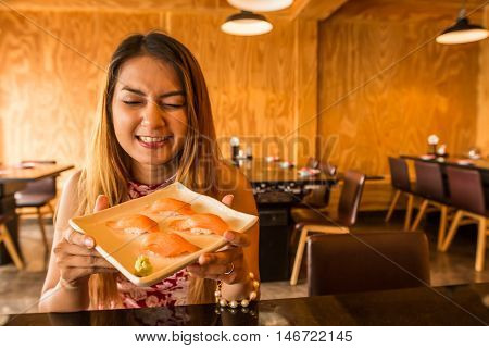 Asian woman holding plate with Salmon Sushi in Japanese restaurant.