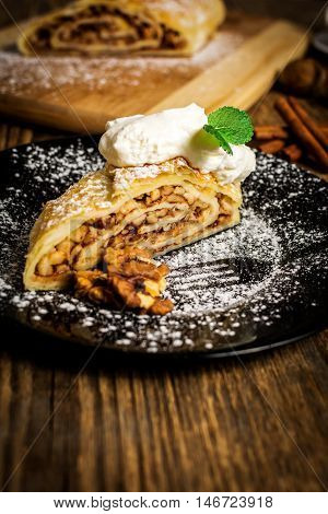 Traditional apple strudel or pie with walnuts and whipped cream