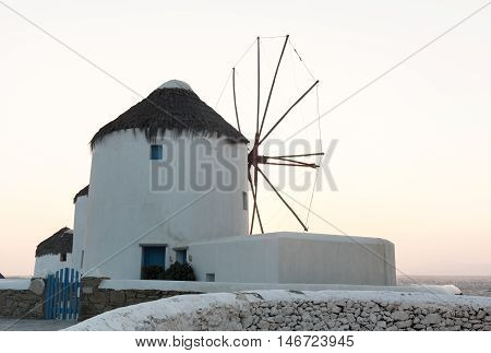Greek traditional windmill during sunset in the greek island of Mykonos
