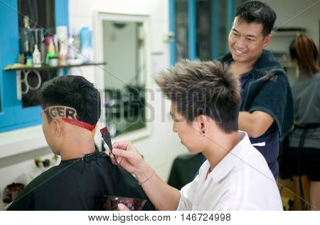 CHIANG MAI THAILAND - JUNE 10: Thai Euro soccer fan have his hair cut and decorated for The Soccer UEFA Euro 2016 tournament is held from 10 June to 10 July 2016 in France at a barber shop June 10 2016 in Chiang Mai Thailand.