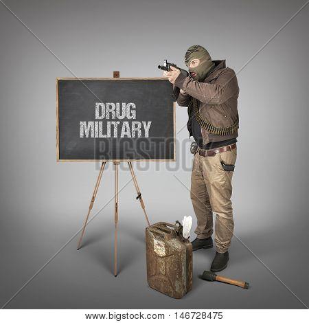 Drug military text on blackboard with terrorist holding machine gun