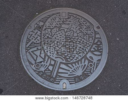 KAGAWA, JAPAN - JULY 21, 2016: A manhole cover in Marugame, Kagawa, Japan. Uchiwa was engraved on a manhole cover. Uchiwa is a rigid fan made of silk or paper stretched on a fine bamboo frame.
