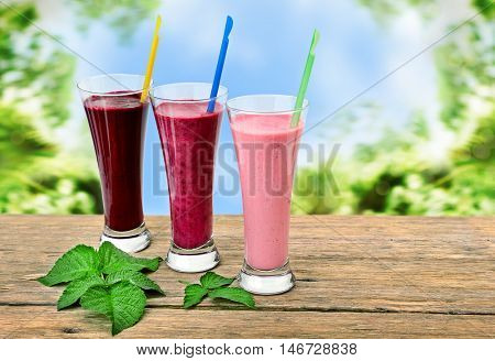 Smoothies made with fresh berries: blackberries, raspberries, red currants, black currants, strawberries on a wooden boards. Healthy drinks on background blur garden.
