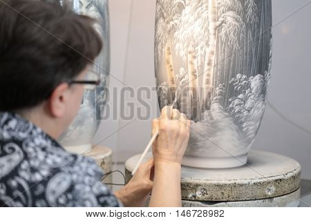 ST. PETERSBURG, RUSSIA - AUGUST 9, 2016: Worker of Imperial porcelain manufactory at workplace. Founded in 1744 by order of Empress Elisabeth, now the factory produces about 4000 items