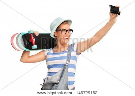 Female hipster taking a selfie and holding a skateboard isolated on white background