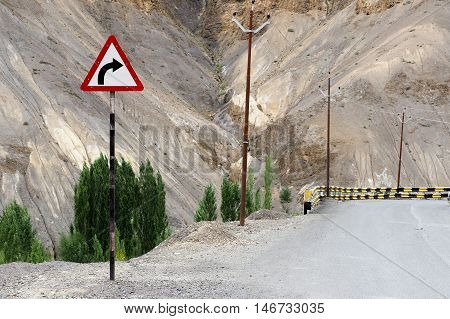 Dangerous curve road with warning sign caution in high mountain nature.