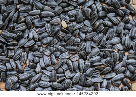 Black sunflower seeds on the table, background from seeds of sunflower