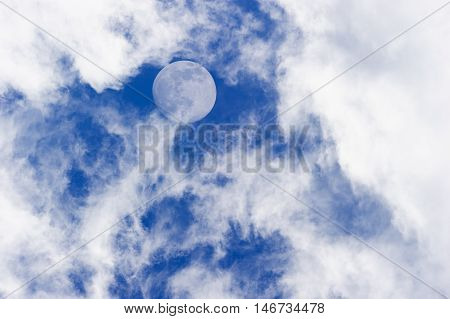Moon clouds is a daytime scenic of wispy white cumulus clouds set against a deep blue sky as a full moon rises in the sky.