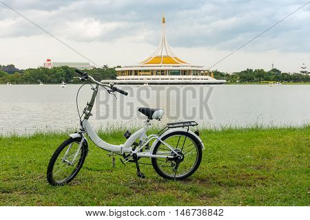 Mini bike on canal and modern architecture building background.