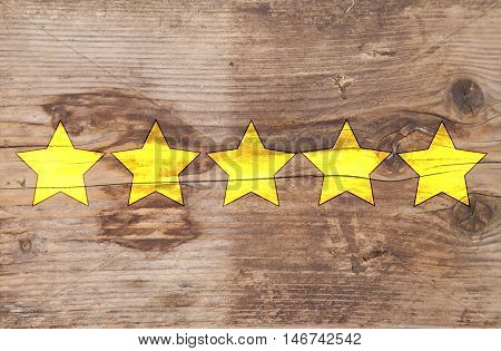 Five yellow ranking stars on wooden background