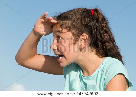 Young Girl Looking Ahead With The Hand In Forehead, Surprised