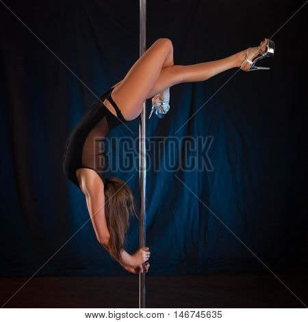 sexy young slender brunette dancing on the pole. Female caucasian appearance with an excellent bum shows tricks on the pole
