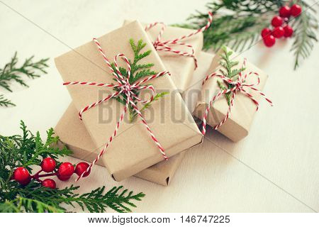 Xmas gifts wrapped in a natural coloured paper and decorated with a traditional Christmas twine and fir branches retro stylized photo