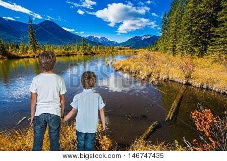 Two little boys holding hands on the lake.  Indian summer in the Rocky Mountains of Canada. Concept of ecological tourism