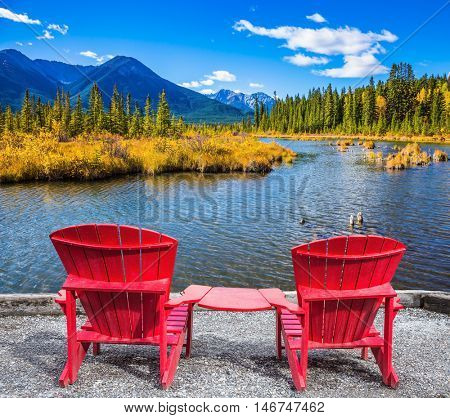 Two convenient red chaise lounges on the bank of the lake. Concept of ecological tourism. Indian summer in the Rocky Mountains of Canada