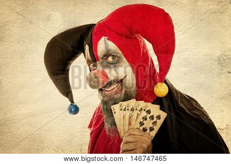 Evil Fool Holding Playing Cards, Vintage Filtered, Concept Gambling