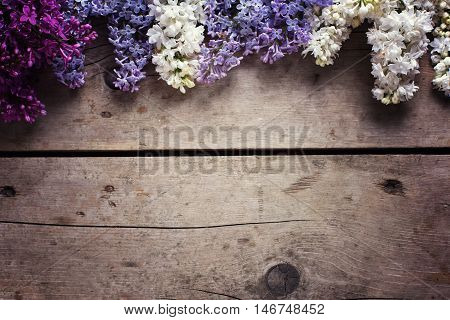 Border from aromatic lilac flowers on vintage wooden planks. Selective focus. Place for text. Floral still life. Toned image.